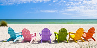 Adirondack Beach Chairs. On a Sun Beach in front of a Holiday Vacation Travel house Royalty Free Stock Photo
