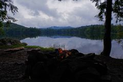 Adirondack Campfire on moody lake with Mountains in the background. stock photos