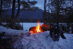 Adirondack Campfire in the snow with Mountains in the background. royalty free stock photography