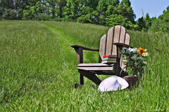Adirondack chair. With flowers and sunhat in a field of tall grass Royalty Free Stock Image