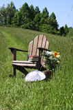 Adirondack chair. With flowers and sunhat in a field of tall grass Royalty Free Stock Images