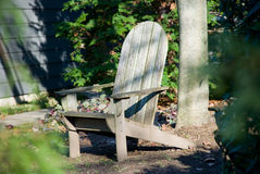 Adirondack Chair. A comfy Adirondack chair near a house and tree.  Comfortable rest and relaxation in the garden Royalty Free Stock Photography