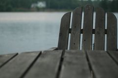 Adirondack chair on lake 2. Adirondack chair hiding behind table . Focus is on the chair, with cottage in background Stock Photos