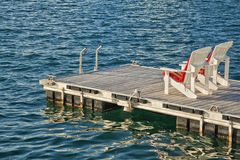 Adirondack chairs. Two adirondack chairs on a floating dock Stock Images