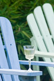 Adirondack chairs. A glass of white wine rests on the arm of a colorful adirondack chair Royalty Free Stock Image