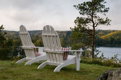 Adirondack chairs. Two Adirondack chairs in a garden overlooking a lake Royalty Free Stock Images