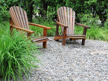 Adirondack chairs. Two adirondack chairs on a peaceful pebble beach Royalty Free Stock Photography