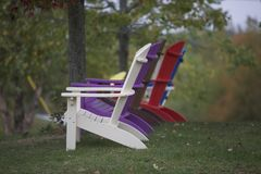 Adirondack Chairs in Color. Sideview of four colorful Adirondack chairs against trees and greenery.  Green grass.  Restful feeling Stock Photos