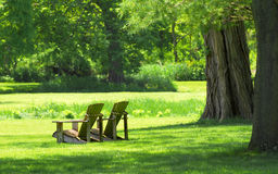 Adirondack chairs in a country setting. Two Adirondack chairs overlooking a country setting Stock Photo
