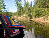 Adirondack Chairs on Deck at lake. Multicoloured adirondack chairs on a cottage deck with a beautiful lakeside and forest view in Northern Ontario,Canada Stock Photos