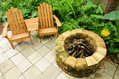 Adirondack chairs and fire pit. Adirondack chairs on a relaxing patio with a fire pit and green plants Stock Photography