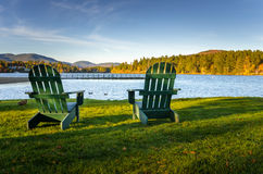 Adirondack Chairs in front of a Lake. Adirondack Chairs on the Shore of Mirror Lake in the Mountain Village of Lake Placid at Sunset Royalty Free Stock Photos