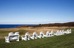 Adirondack chairs on Michigan golf course. A row or Adirondack chairs at the Arcadia Bluffs Golf Course, in Arcadia, Michigan.  Arcadia Bluffs Golf Course is a Royalty Free Stock Photography