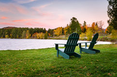 Adirondack Chairs near the Shore of a Lake at Dusk. Empty Adirondack Chairs on Grass dotted with Fallen Leaves in Front of a Lake at Dusk. Beautiful Autumn Royalty Free Stock Photos