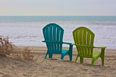 Adirondack chairs ocean. Two colorful Adirondack chairs sit on the beach and face the waves of the Pacific Ocean in Ventura California Stock Image