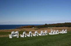Adirondack Chairs Overlooking Lake Michigan. White Adirondack chairs in a row sitting on green, and overlooking Lake Michigan.  A golf course is shown between Royalty Free Stock Photo