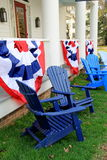Adirondack chairs and patriotic banners. Blue and white Adirondack chairs set together on lawn with patriotic banners hanging from front porch of country home Royalty Free Stock Photos