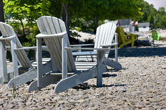 Adirondack chairs on rocky beach Stock Photo