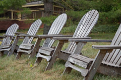 Adirondack chairs. In a row in front of a rustic mountain cabin Stock Images