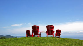 Adirondack Chairs Summer Blue Sky. Four red Adirondack chairs on a grassy slope overlooking a body of water Royalty Free Stock Photo