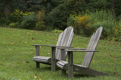 Adirondack Chairs. Two adirondack chairs setting on a lawn Royalty Free Stock Photos