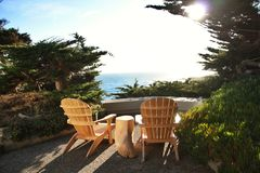 Adirondack Chairs. Two wooden Adirondack chairs on a porch overlooking the sea Royalty Free Stock Photography