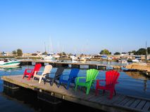 Adirondack Chairs by the water. Empty Adirondack Chairs on the deck by the water Royalty Free Stock Photography