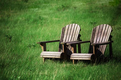 Adirondack Chairs. Wooden adirondack chairs in a grassy field Stock Images