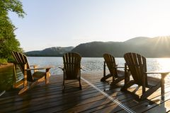 Adirondack deck chairs on lake dock Stock Images