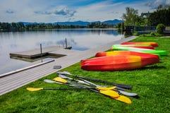Adirondack Kayaking. Row of kayaks and paddles waiting on dock of Mirror Lake in Lake Placid, New York Stock Photo