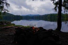 Adirondack-Lagerfeuer auf schwermütigem See mit Bergen im Hintergrund Stockfotos