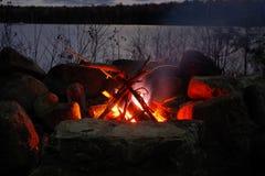 Adirondack-Lagerfeuer auf schwermütigem See mit Bergen im Hintergrund Lizenzfreies Stockfoto