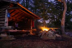 Adirondack Lean to Bushcraft camp shelter with fire at night in the mountains. Bushcraft log cabin lean to shelter with campfire blazing at night. Located in royalty free stock photos