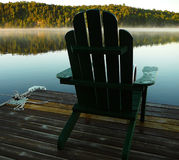 Adirondack/Muskoka Chair. On the end of a dock at sunrise Stock Images