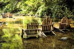 Adirondack préside prêt pour lounging en rivière Photographie stock libre de droits