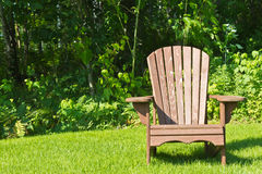 Adirondack-Sommergartenstuhl draußen auf dem grünen Gras Lizenzfreie Stockfotografie
