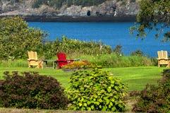 Adirondack-Stühle über dem Loooking den Strand Stockfotografie