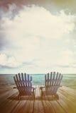 Adirondack-Stühle auf Dock mit Weinlesebeschaffenheiten und -gefühl Lizenzfreie Stockfotografie