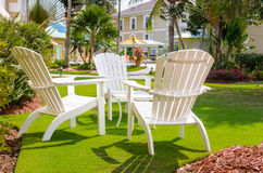 Adirondack-Stühle in einem tropischen Garten Lizenzfreie Stockfotos