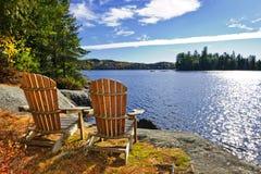 Adirondack Stühle am Seeufer Stockbilder