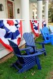Adirondack-Stühle und patriotische Fahnen Lizenzfreie Stockfotos