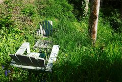 Adirondack stolar i en bevuxen trädgård Arkivbilder