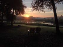 Adirondack stolar och soluppgång över en sjö Arkivbilder