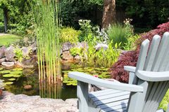 Adirondack-Stuhl in dem Teich Stockfoto