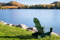 Adirondack-Stuhl, der einen Mountainsee auf Sunny Morning gegenüberstellt Lizenzfreie Stockfotos