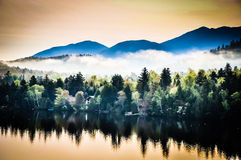 Adirondack Sunrise Mist. Reflections of Adirondack Mountains and early morning mist and fog on Mirror Lake in Lake Placid, New York Royalty Free Stock Images