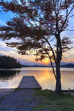 Adirondacks Dock Sunset. Sun sets behind a dock and maple tree on serene Seventh Lake in the Fulton Chain Lakes in the Adirondacks Mountains of New York Royalty Free Stock Images