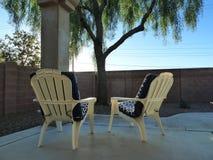 Adirondak chairs in Arizona backyard. Adirondak chairs with blue and white chair pads on backyard patio overlooking backyard in Arizona stock photos