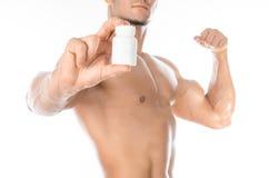 Aditivos do halterofilismo e do produto químico: o halterofilista forte considerável que guarda um frasco branco dos comprimidos  Imagens de Stock Royalty Free