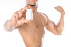 Aditivos do halterofilismo e do produto químico: o halterofilista forte considerável que guarda um frasco branco dos comprimidos  Fotos de Stock